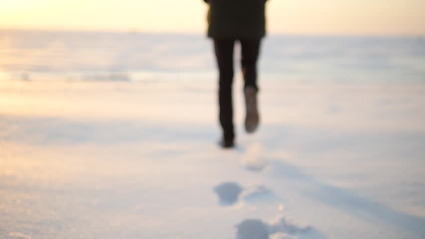 Legs of man walking on snow with footprints on snowy day