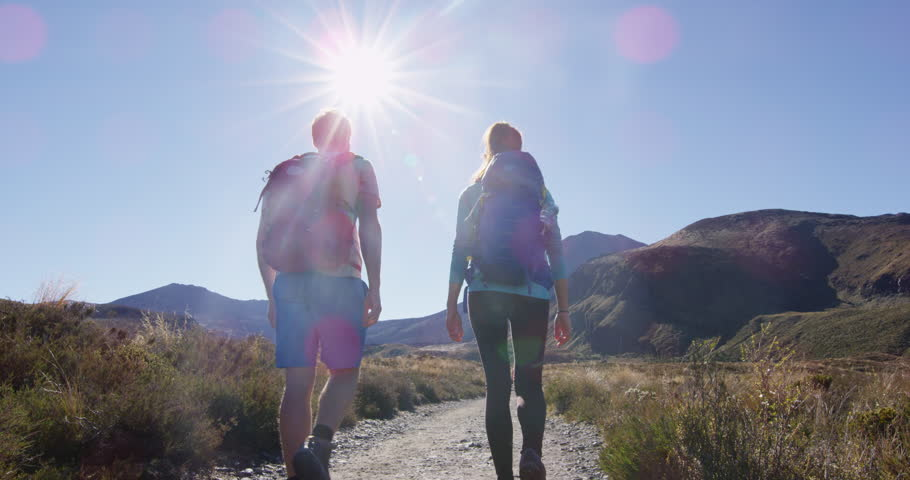 Young couple trekking hiking on tramping track in Tongariro National Park, New Zealand. Man and woman hikers in mountains. Bright sun is shining over backpackers at Tongariro Alpine Crossing.
