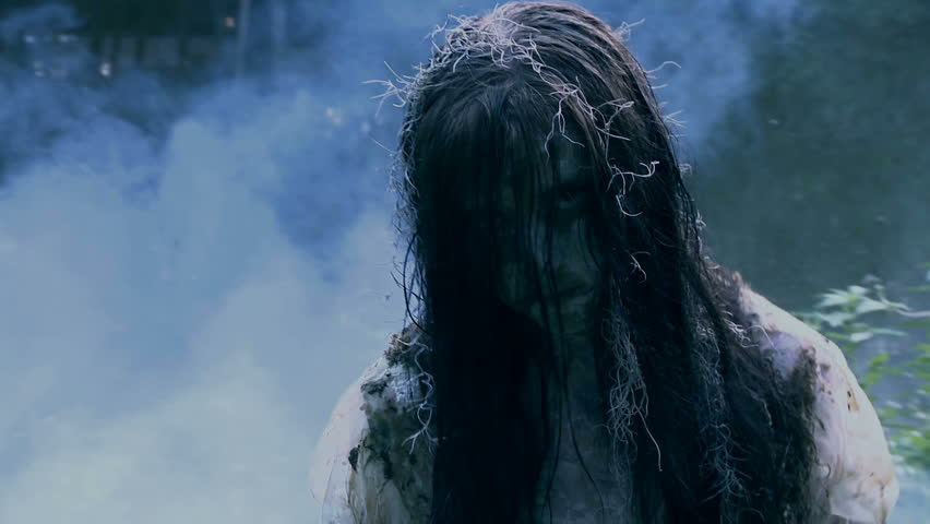 Walking through fog an undead zombie girl possessed with evil attacks the camera  | Shutterstock HD Video #3327200