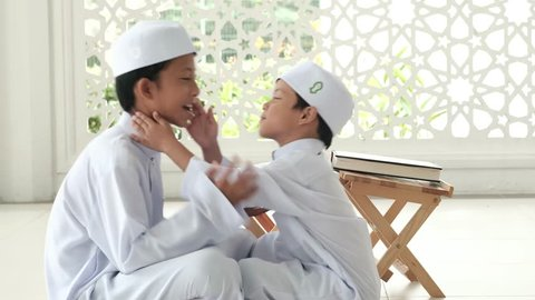 A younger boy shake hand and kiss his elder brother after finish reading the Quran