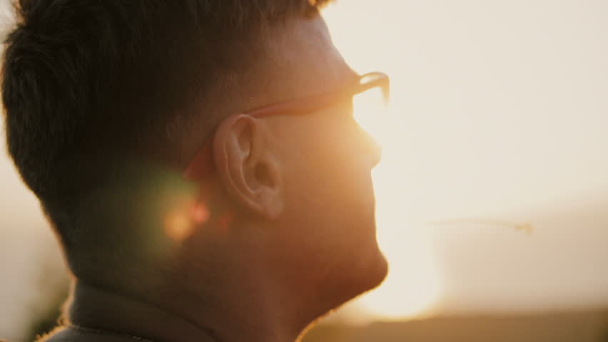 Slowmotion of Handsome young fashion man wearing sunglasses and backpack looks sunset in the field. In the mouth of a blade of grass. 1920x1080 closeup | Shutterstock HD Video #33311497