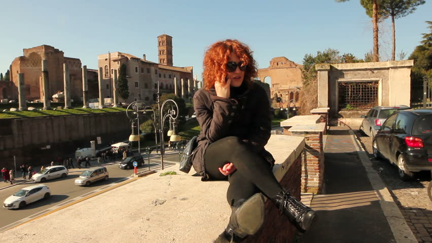 Young smiling woman talking on cell phone, against colosseum