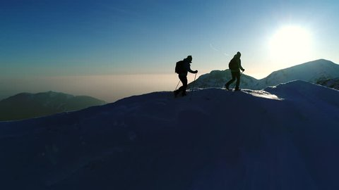 Aerial - Flyover hikers equipped with warm clothes, backpacks and trekking poles exploring the winter wonderland in Julian Alps. Two adult male mountaineers walking on snowy mountain top at sunset