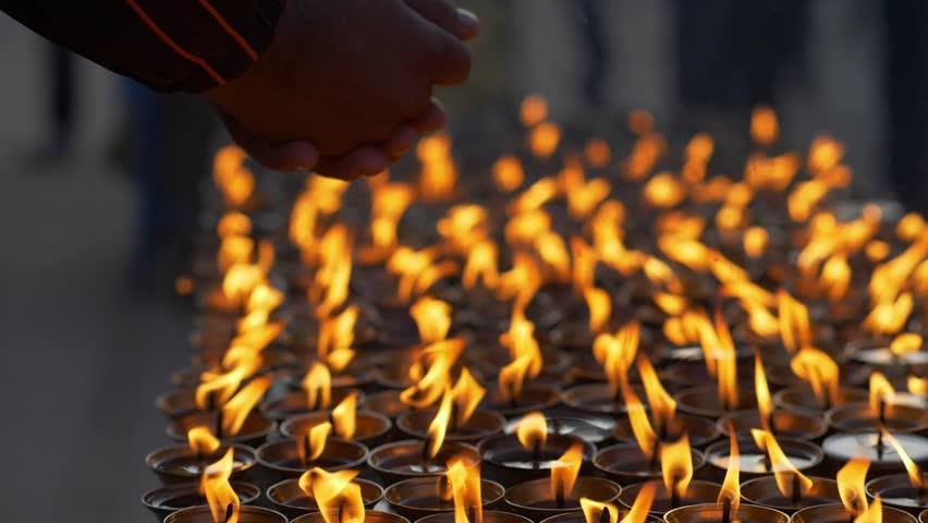 Hands of prayer and burning candles at Buddhist site of Boudhanath. Kathmandu, Nepal. Slow motion shot