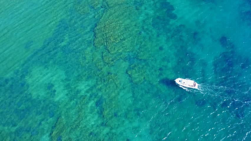 Aerial bird's eye view video taken by drone of boat cruising in caribbean tropical beach with turquoise - sapphire waters