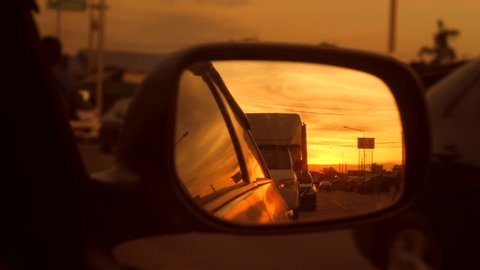 Beautiful Orange Sunset in Rear View Car Mirror. 4K. Thailand.