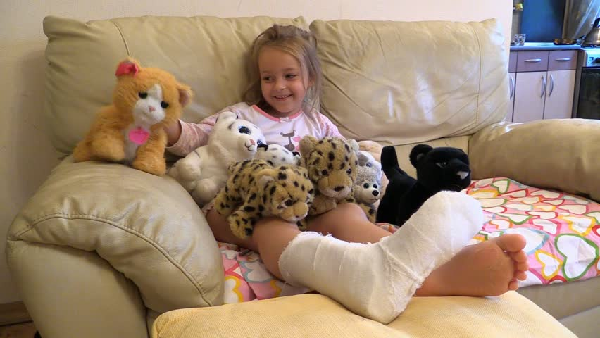 Girl with broken leg in plaster sit and play soft toys at home couch