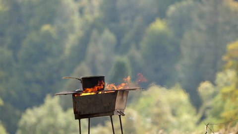 Cooking traditional food outdoor in nature, rustic cuisine in the countryside, healthy lifestyle of mountain shepherds and secluded village peasants