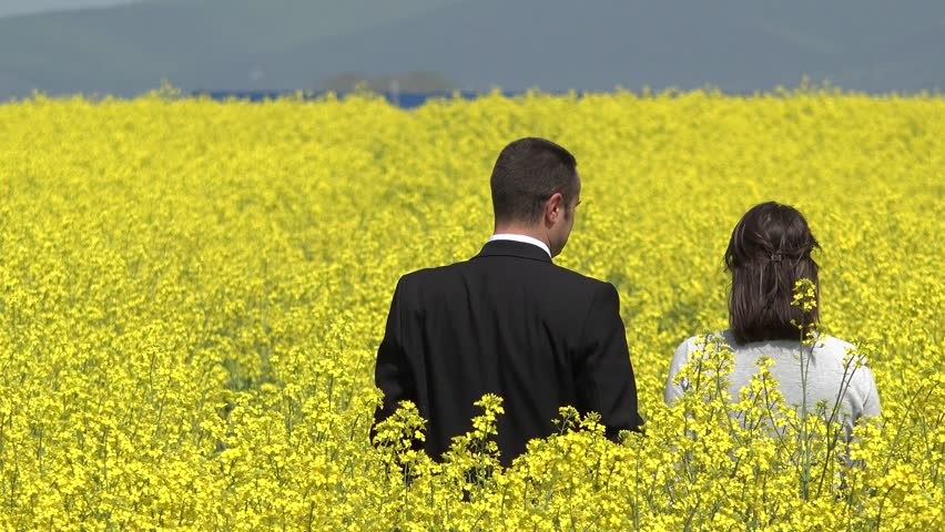 Man and woman standing with back in blossom yellow rape field