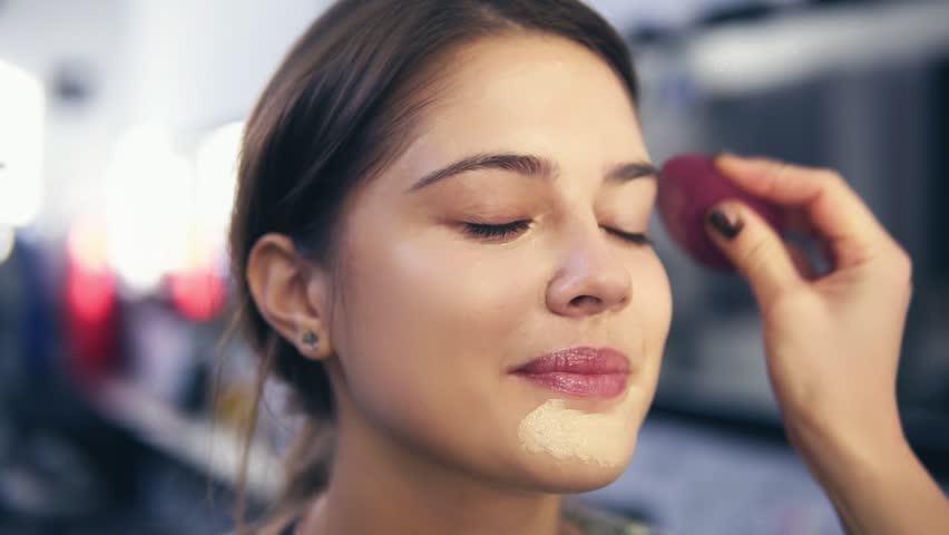 Unrecognizable visagist applying fluid foundation on young woman's face using sponge. Professional makeup in salon. Slowmotion shot