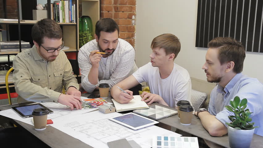 Young employees work sitting at table in office of company indoors. Four men actively discuss details of blueprint presented front of them, making notes in notebook and choosing colors, looking at | Shutterstock HD Video #33481897