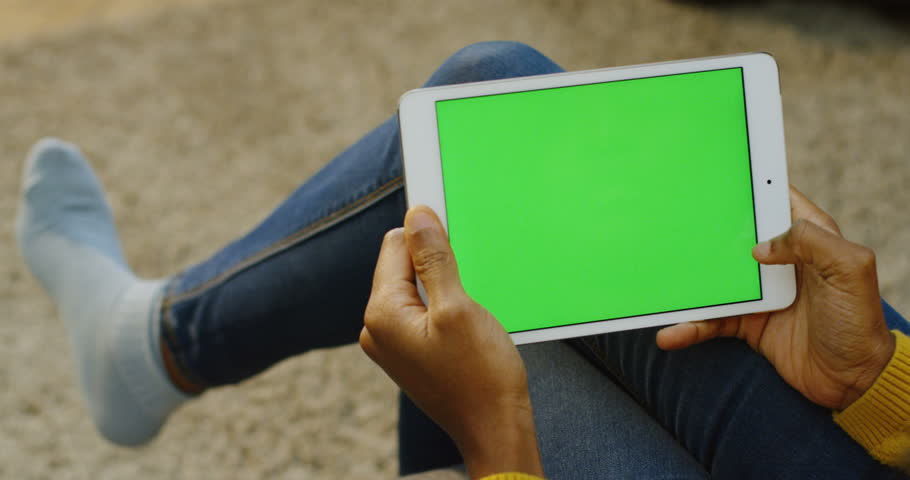 African american woman's hands scrolling and taping on the white horizontal tablet device while she sitting at home without shoes. Over shoulder. Green screen. Chroma key | Shutterstock HD Video #33502687
