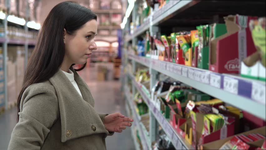 Young woman choosing spices in grocery store, beautiful woman shopping in a supermarket | Shutterstock HD Video #33505597