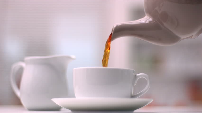 Teapot pouring tea in slow motion