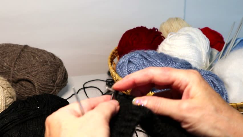 Female hands knit a black hat on five spokes in a circle. ?olored skeins of wool yarn in the background