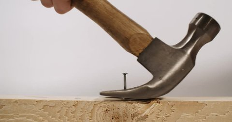 Hammer pulls a nail out of wood.