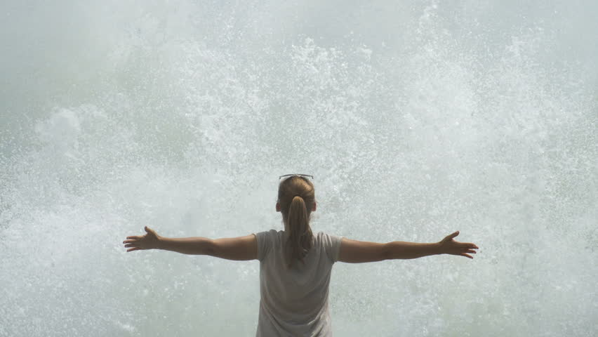 Young Woman with Raised Hands Infront of Giant Sea Waves. Slow Motion #33612397