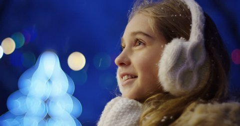 Close up of the happy cute girl looking charmed at something and clapping in white winter gloves on the blurred Christmas lights in the night. Portrait shot. Outside