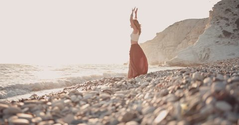 Young woman in boho style day with arms outstretched dreaming at the beach in summer