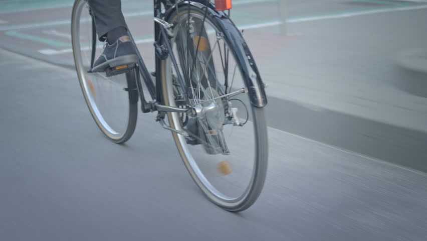 Close-up of male cyclist pedaling to a job. Active person maintaining a healthy lifestyle and riding a bicycle on a street in the city.