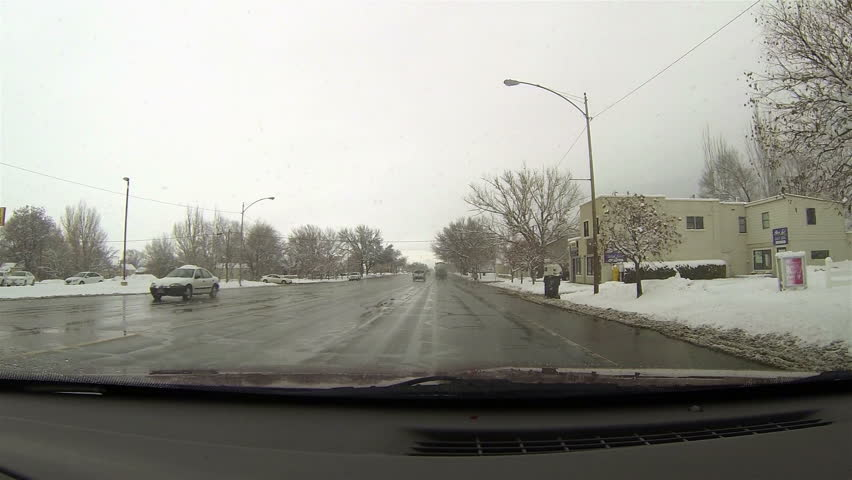 Small rural town winter snow storm main street. Driving a car on rural country road in winter. Snow and ice on highway and near mountains and hills. First person point of view through windshield.  | Shutterstock HD Video #3363527