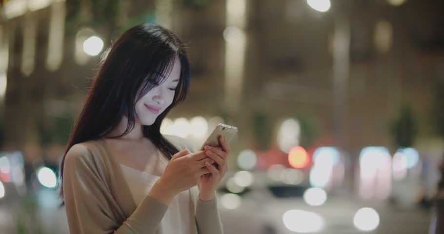 Attractive asian Woman using Mobile Phone During Walk on Streets of Night Town with smile, steadycam shot