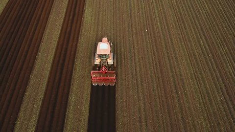 Aerial view Farmer in tractor preparing land with seedbed cultivator in farmlands. Tractor plows a field. Agricultural work in processing, cultivation of land. Farmers preparing land and fertilizing