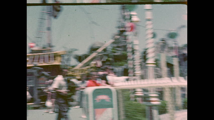 1950s: Crowd at Jolly Roger pirate ship at Disneyworld. Crowd at whale statue. Boy drives car in amusement park ride. Line across drawbridge at Sleeping Beauty Castle. People on river boat. Foliage.
