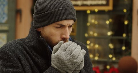 Portrait of the caucasian man in a hat and gloves coughing hard on the street in winter. Christmas decorated showcase behind him. Close up. Outdoor