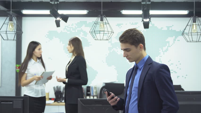 Business concept. Young businessman in formal attire looks smartphone on background of two young female employees discussing work in the office | Shutterstock HD Video #33667774
