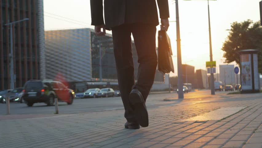 Successful young man walking on the street in the city. Businessman wearing a suit and holding a briefcase ready for a brand new day early in the morning. | Shutterstock HD Video #33670387