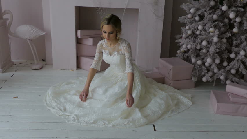 The bride sits on the floor and adjusts her dress   Shutterstock HD Video #33676597