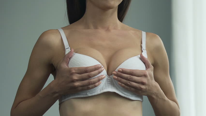 Woman in bra looking in mirror, lifting breasts up, sighing heavily, unhappy