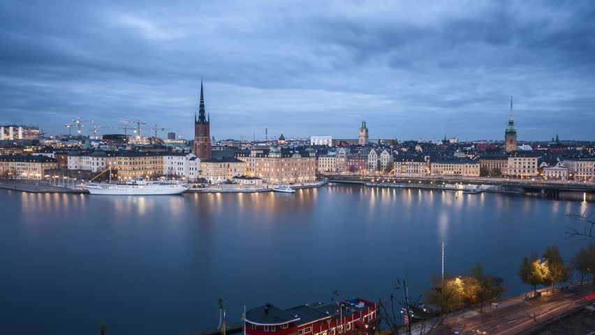Day to night time lapse motion footage of famous Stockholm city center with historic Riddarholmen in Gamla Stan old town district during blue hour at dusk, Sodermalm, central Stockholm, Sweden