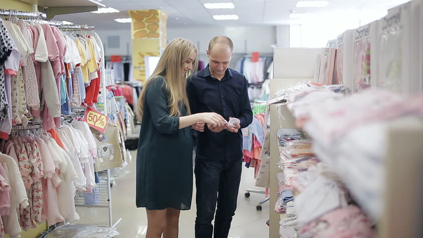 178d4fcff27 pregnant woman with her husband in a children s clothing store. Happy  family choose clothes for baby