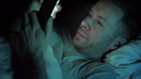 Young Handsome Hipster Man using a Smartphone Lying on Bed at Home Late at Night. White Caucasian in Early 30's. Face Illuminated by Natural Lighting from Screen of Mobile Phone.