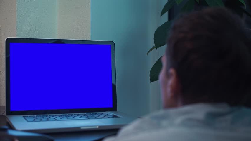Man watching at blue key notebook computer screen at kitchen near stove | Shutterstock HD Video #33694297