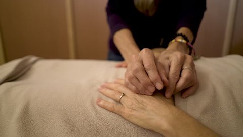 Detail of a professional acupuncturist inserting a needle into the hand of a mature caucasian woman at a spa for treatment.