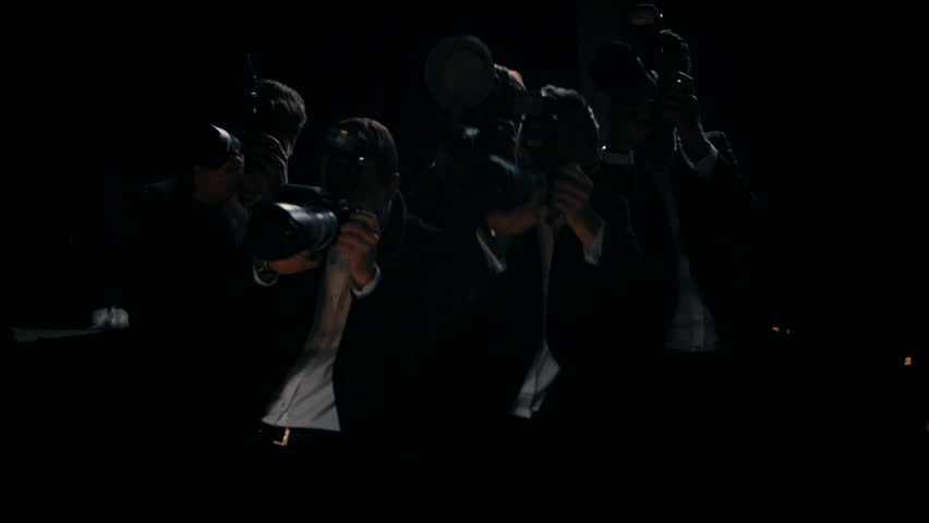 Camera flashes group of paparazzi