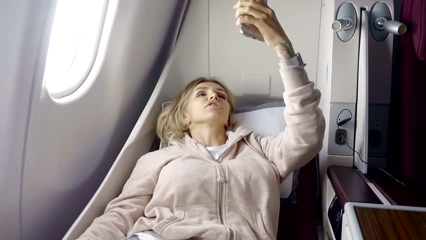 slim blonde woman is rising up a seat in a first class in a plane, during a flight, recording video