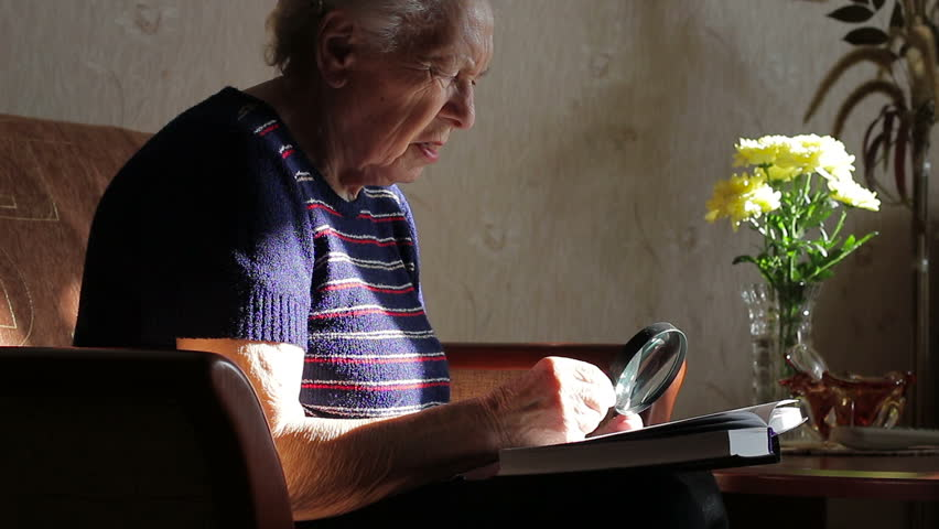Grandmother reading a book with a magnifying glass