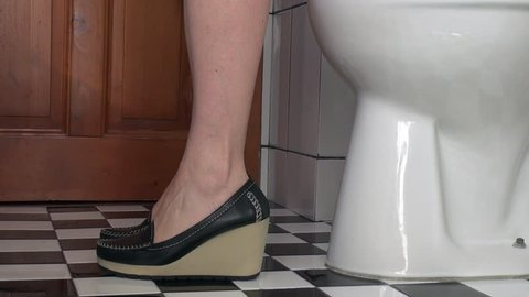 Businesswoman's feet as she sits on a toilet in the bathroom