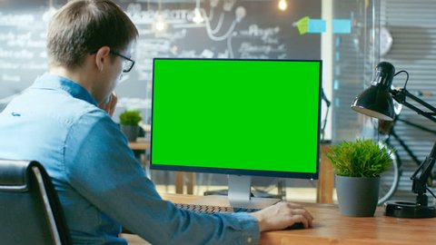 Young Man Works at His Desk on the Personal Computer with Mock-up Green Screen. In the Background His Colleague Works