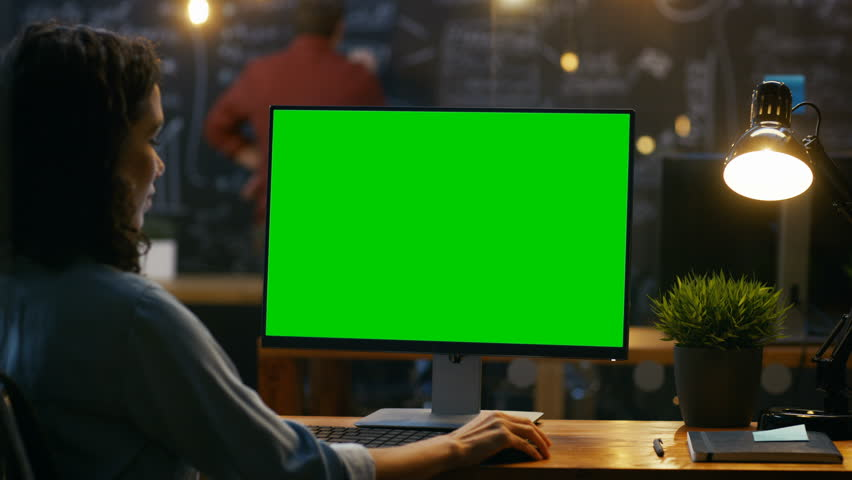 Beautiful Female Office Employee at Her Desktop Works on a Mock-up Green Screen Personal Computer. Over the Shoulder Footage. Her Colleague works in the Background. Creative Office Evening. 4K UHD. | Shutterstock HD Video #33748657