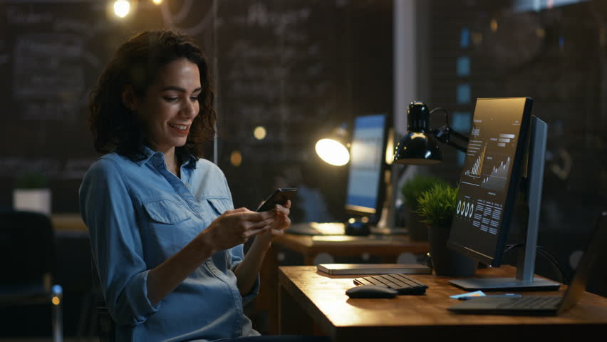 Beautiful Female Financier Uses Mobile Phone, Writing Messages, Emails while Smiling.In the Background Creative Office with Employees.    Shutterstock HD Video #33749680