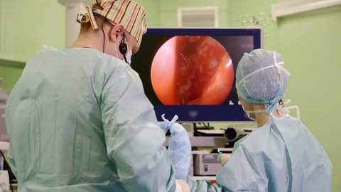 surgeon and his assistant are performing operating endoscopic method, doctor is inputting endoscope into a humans body