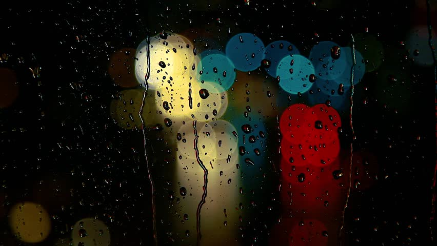 Rainy days, rain drops on window surface and colorful traffic bokeh light.