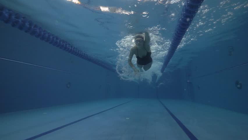 Sports woman floating crawl stroke in blue water swimming pool underwater view. Close up woman swimming crawl stroke on water in floating pool 60 fps