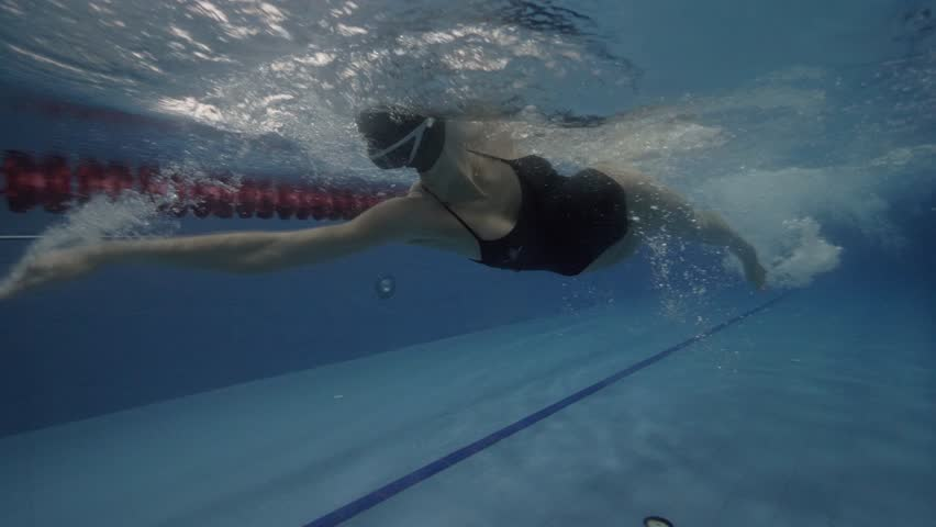 Woman professional swimmer floating crawl stroke in swimming pool underwater view. Close up woman swims crawl style in water path floating pool 60 fps | Shutterstock HD Video #33795682