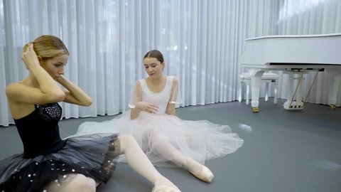 Beautiful ballerinas are talking in ballet studio indoors. Young dancers sitting on floor and speaking with friendly smiles, one of them touching hairstyle with hands. Talented ladies dressed in